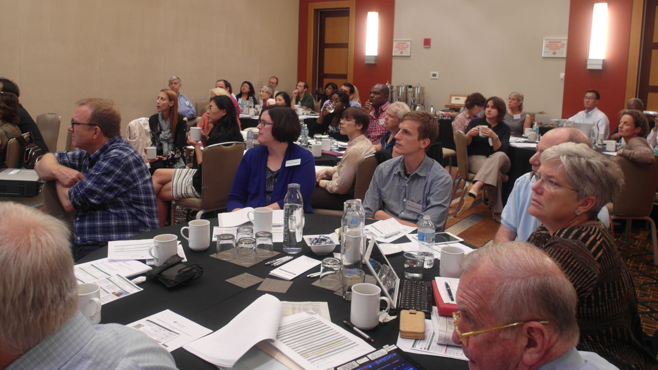 Conference attendees sitting at tables listening to a presentation